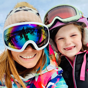 Smiling woman with ski goggles beside smiling child
